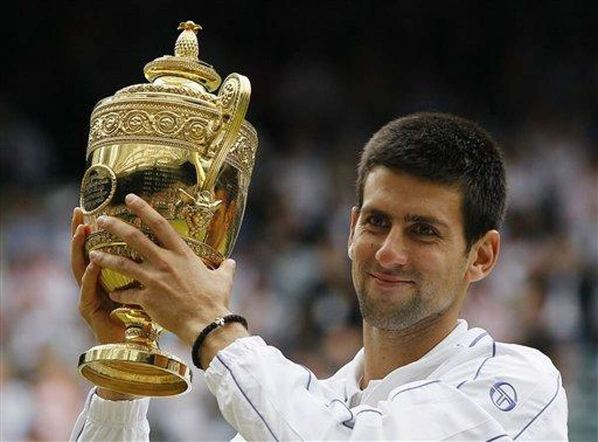 Serbia's Novak Djokovic lifts the trophy after defeating Spain's Rafael Nadal in the men's singles final at the All England Lawn Tennis Championships at Wimbledon, Sunday, July 3, 2011. (AP Photo/Kirsty Wigglesworth)
