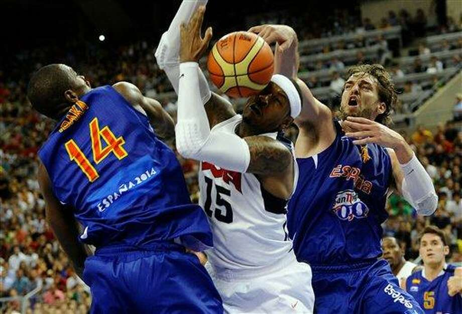 Carmelo Anthony of the US Men's Senior National Team, center, dives for the ball against Serge Ibaka of the Spain Men's Senior National Team, left, and Pau Gasol during an exhibition match between Spain and the United States Tuesday, July 24, 2012, in Barcelona, Spain, in preparation for the 2012 Summer Olympics. (AP Photo/Manu Fernandez) Photo: ASSOCIATED PRESS / AP2012