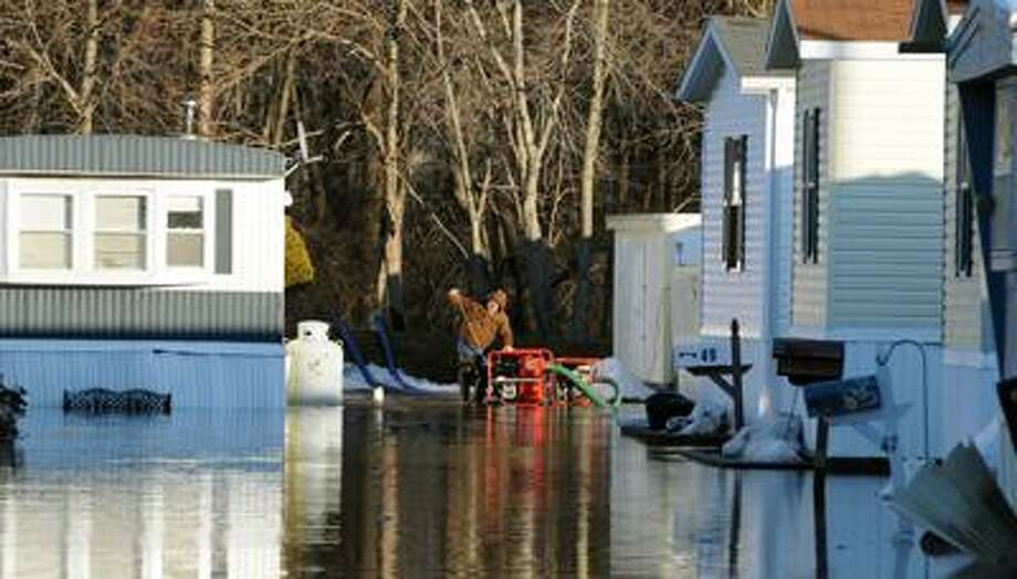 Yalesville Square in Wallingford was flooded by the Qunnipiac River. One resident said this is the fourth time in 26 years the river has flooded. The waters don't reach into the homes because they are raised. A sump pump was being attended to. Photo by Mara Lavitt/New Haven Register3/7/11