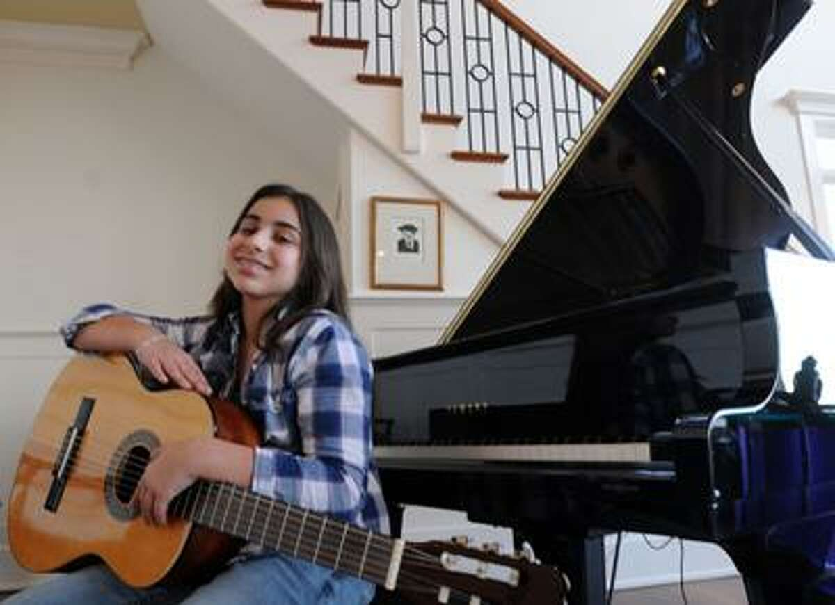 Samantha Foggle, 13, at home in Madison. She plays four instruments and recently won the Esongwriter.com International Songwriting Contest, Youth Division. (Mara Lavitt/Register)