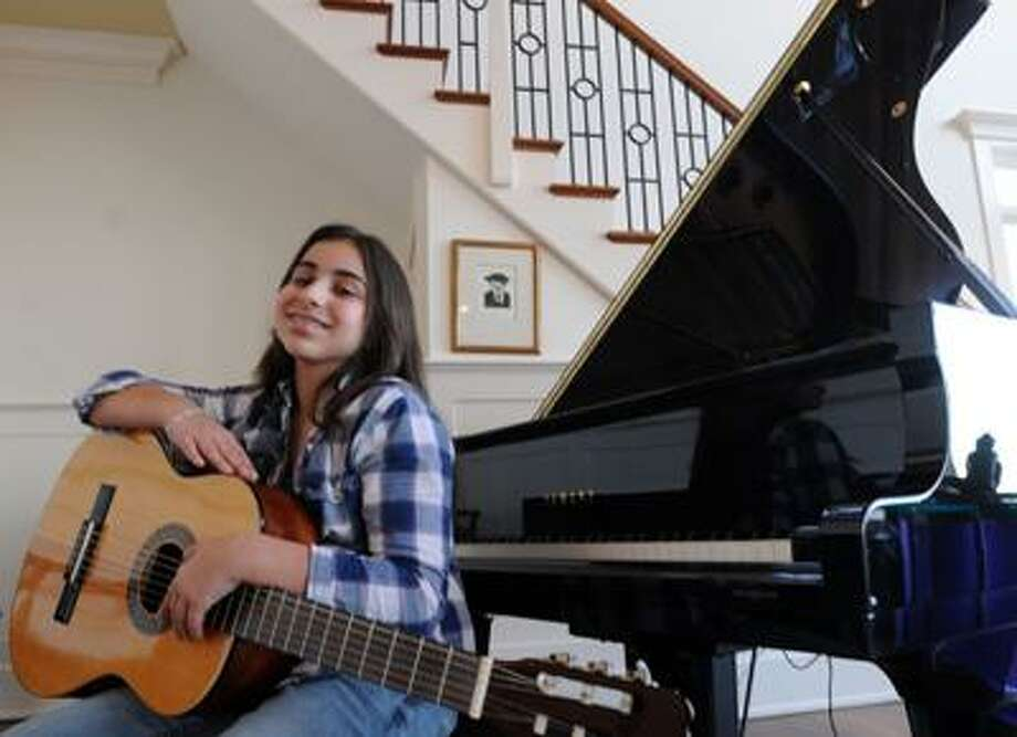 "Samantha Foggle, 13, at home in Madison. She plays four instruments and recently won the <a href=""http://Esongwriter.com"">Esongwriter.com</a> International Songwriting Contest, Youth Division. (Mara Lavitt/Register)"