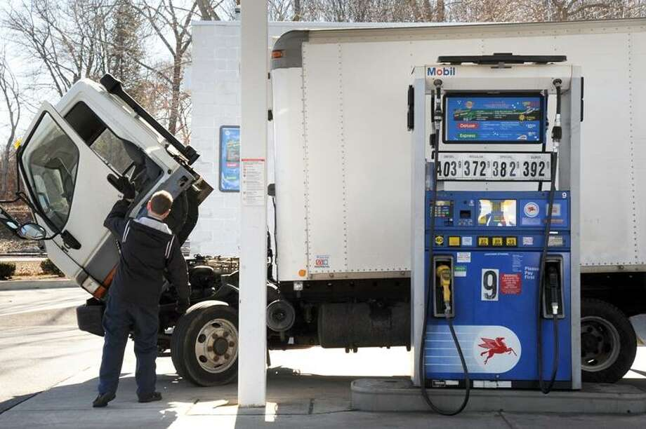A truck driver fills his truck with gas at Chucky's Mobil station in Branford Monday. Oil prices, which drive gas prices, continued their upward trend Monday amid ongoing unrest in Libya