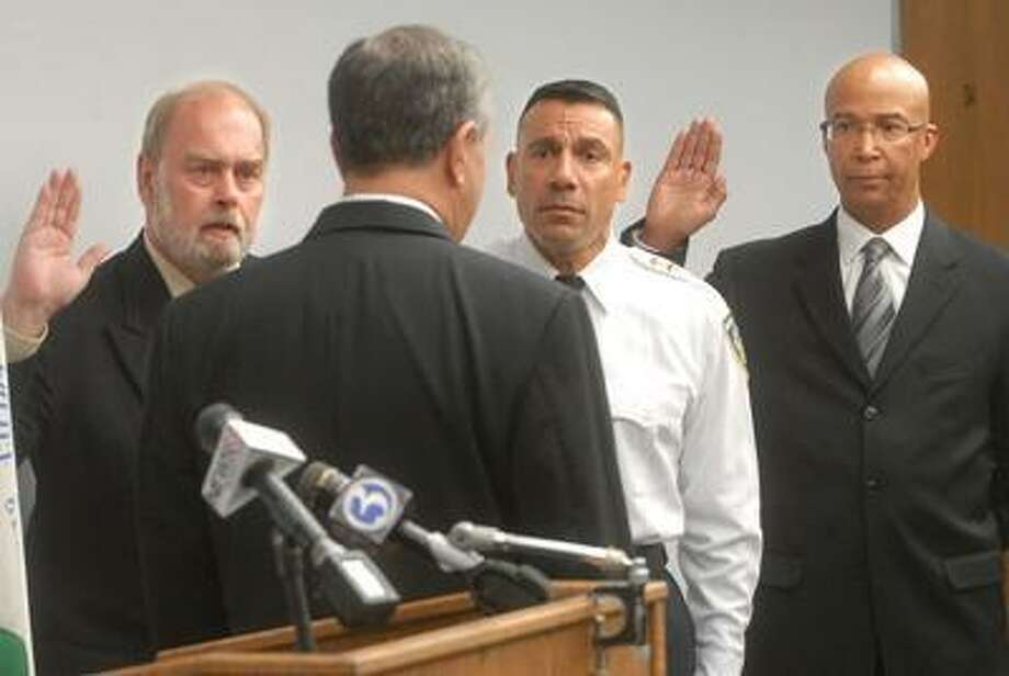 In this file photo from June 2010, Tobin Hensgen, Ariel Melendez and Thomas Wheeler Jr. are sworn as New Haven assistant chiefs of police by Mayor John P. DeStefano.  Brad Horrigan