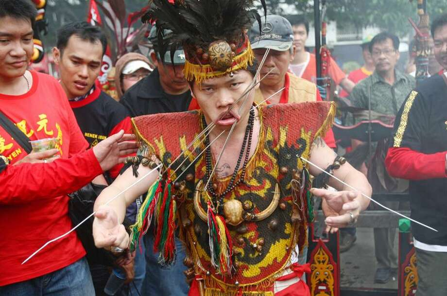 A worshipper pierces his cheeks with metal skewers during Cap Go Meh festival that marks the end of Lunar New Year celebrations in Jakarta, Indonesia, Monday. Associated Press Photo: ASSOCIATED PRESS / AP2012