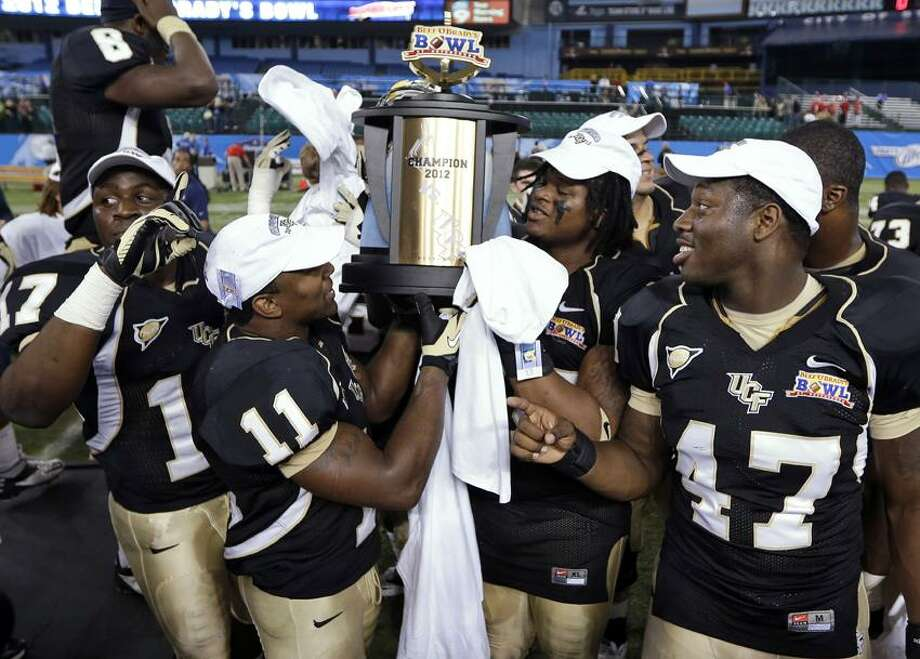 Central Florida players, from left, Cedric Thompson, Jonathan Davis, E.J. Dunston, and Deion Green celebrate with the trophy after Central Florida defeated Ball State 38-17 during the Beef 'O' Brady's Bowl NCAA college football game Friday, Dec. 21, 2012, in St Petersburg, Fla. (AP Photo/Chris O'Meara) Photo: AP / AP
