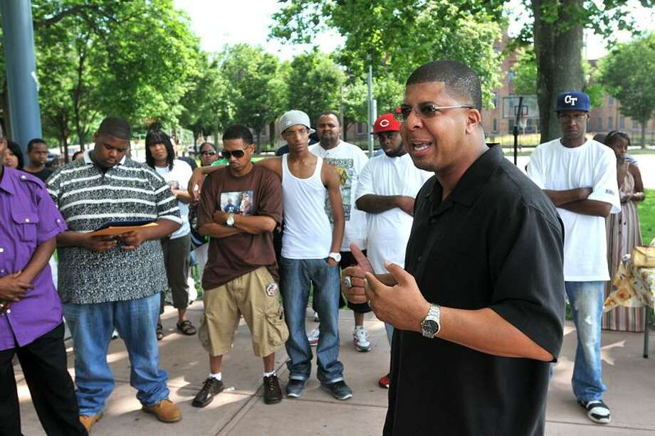 Hillhouse High School Principal Kermit Carolina speaks about stopping youth violence during a memorial vigil/anti-violence rally Saturday in memory of Travis Washington. Washington was shot hours after his Hillhouse graduation last week.  Photo-Peter Casolino/New Haven Register
