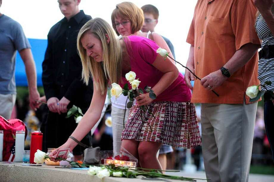 "Family members of the victims of the Century 16 theater shooting leave roses at a memorial display during a vigil at the Aurora Municipal Center campus in Aurora, Colo. Sunday, July 22, 2012. 12 people were killed and 58 were injured in a shooting during an early Friday premiere of ìThe Dark Knight Rises."" (AP Photo/The Denver Post, AAron Ontiveroz, Pool) Photo: ASSOCIATED PRESS / AP2012"