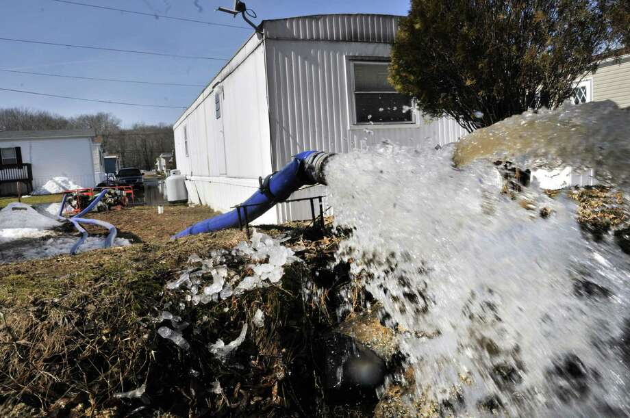Water is pumped from Yalesville Square development back into the Quinnipiac River on Tuesday. Melanie Stengel/Register.