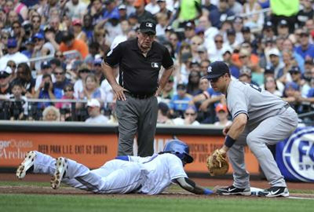 New York Mets' Jose Reyes dives safely back into first base under the glove of New York Yankees first baseman Mark Teixeira after a pick off attempt in the first inning of a baseball game, Saturday, July 2, 2011, at Citi Field in New York. Reyes left the game after the second inning due to an injury.(AP Photo/Kathy Kmonicek)