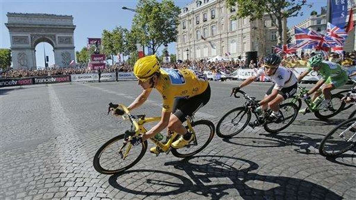 Bradley Wiggins of Britain, wearing the overall leader's yellow jersey is followed by teammate Mark Cavendish of Britain and Peter Sagan of Slovakia, wearing the best sprinter's green jersey as they pass the Arc de Triomphe during the 20th stage of the the Tour de France cycling race over 74.6 miles with start in Rambouillet and finish in Paris, France, Sunday. Associated Press