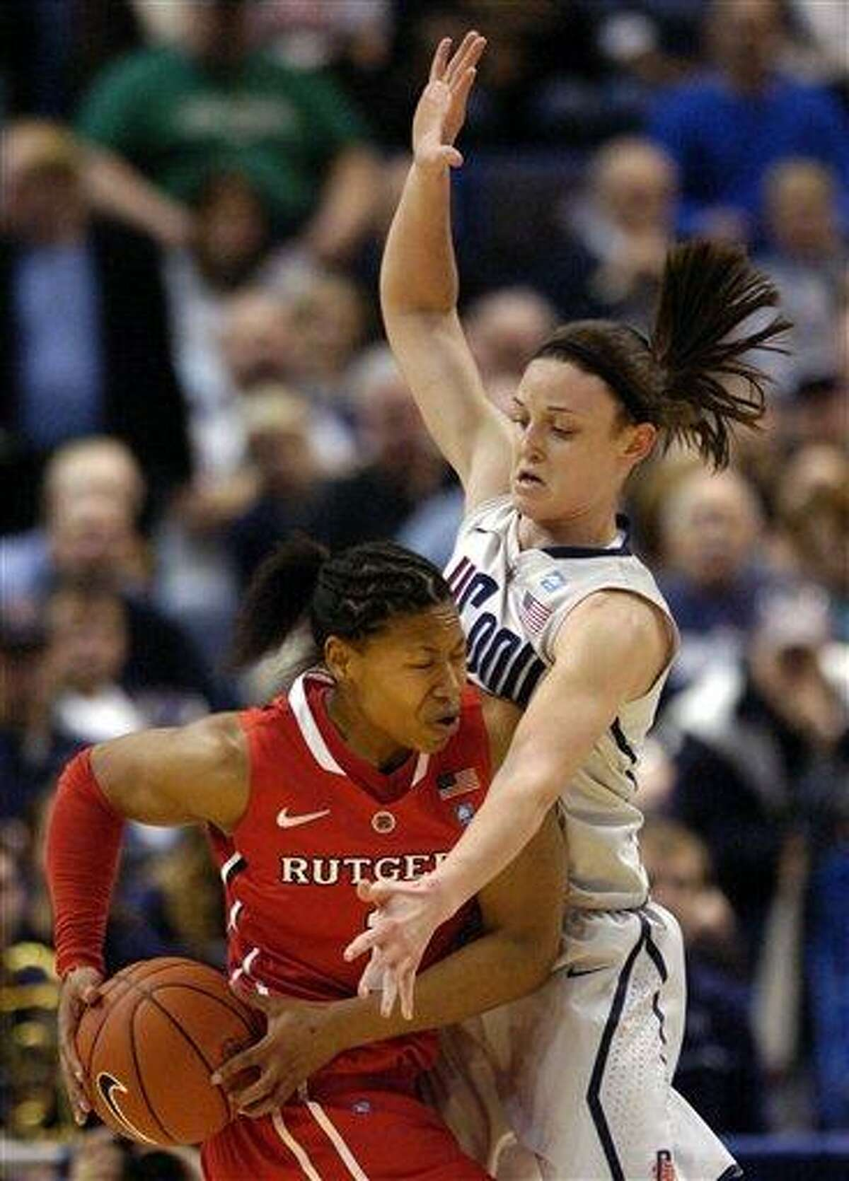Connecticut's Kelly Faris, right, guards Rutgers' Khadijah Rushdan during the first half of an NCAA college basketball game in the semifinals of the Big East tournament Hartford, Conn., on Monday, March 7, 2011. (AP Photo/Fred Beckham)