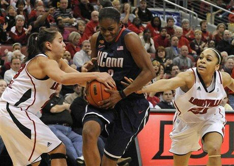 Connecticut's Tiffany Hayes, center, fights for control against Louisville's Shoni Schimmel, left, and Bria Smith during the second half of their NCAA college basketball game on Tuesday, Feb. 7, 2012 in Louisville, Ky. Connecticut defeated Louisville 56-46. (AP Photo/Timothy D. Easley) Photo: AP / Timothy D. Easley