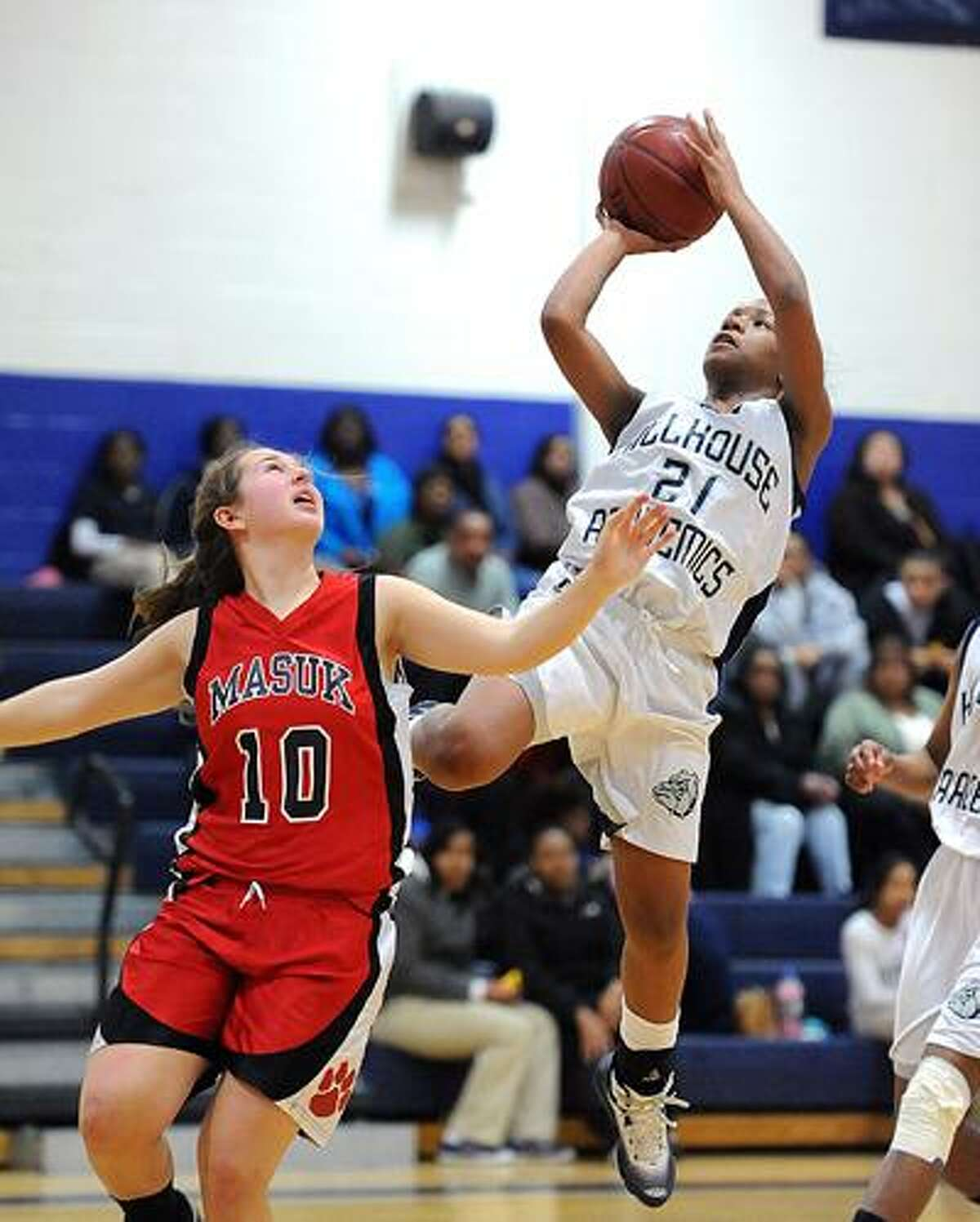 New Haven--Hillhouse's Quanisha Solomon goes up over Masuk's Kelly Zazeri during the third period. Photo by Peter Casolino/New Haven Register03/07/11 Cas110307