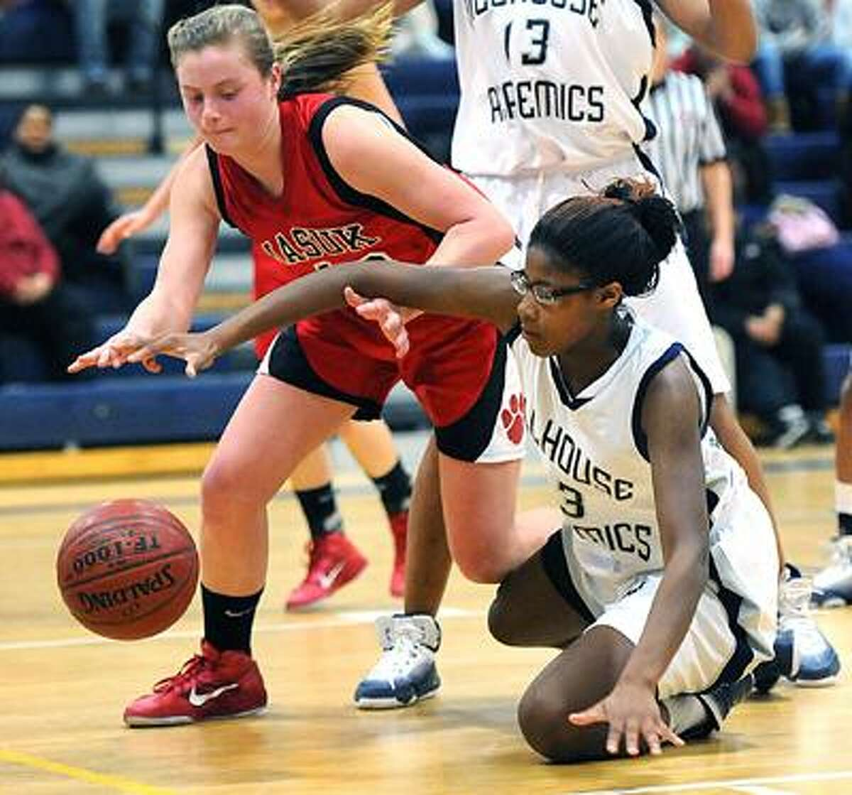 New Haven--Hillhouse's Bria Holmes battles for a loose ball with Masuk's Melissa Peet during the third period. Photo by Peter Casolino/New Haven Register03/07/11 Cas110307