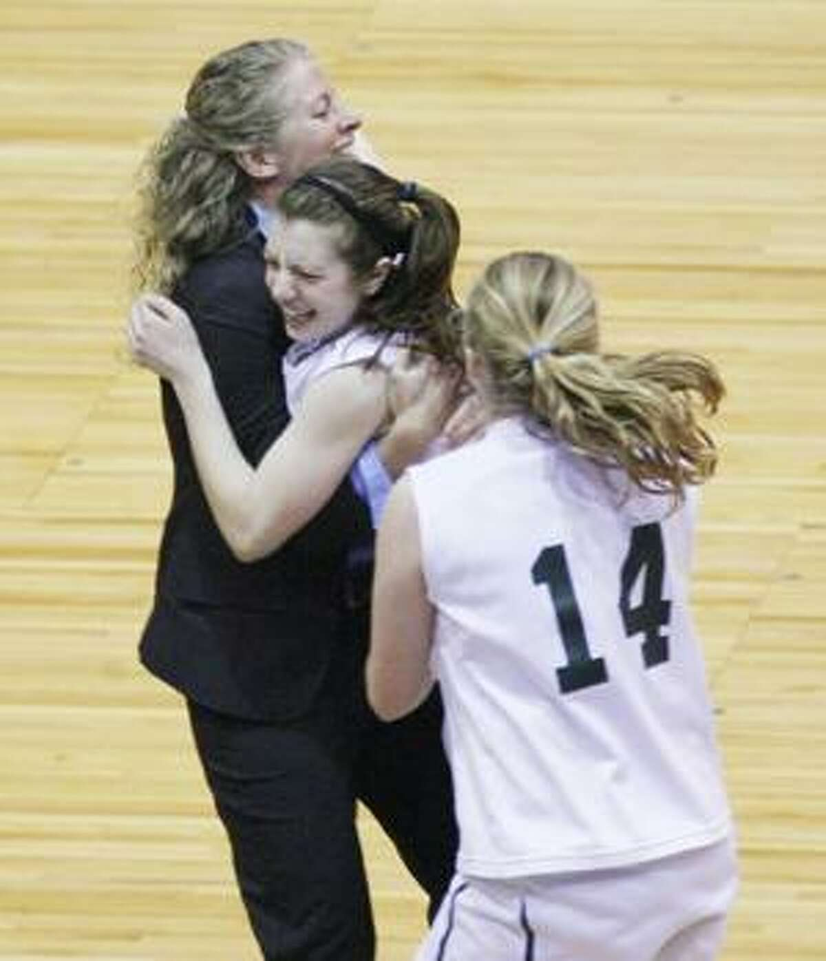 Dispatch Staff Photo by JOHN HAEGER Hamilton's Katie Weeks (11) is hugged by coach Jessica Poole as teammate Katherine Keever (14) looks on before the start of overtime against Sackets Harbor in the Class D championship in Utica on Sunday, March 6, 2011. Weeks went 3-for-3 from the foul line to send it into overtime. Hamilton won 48-45.