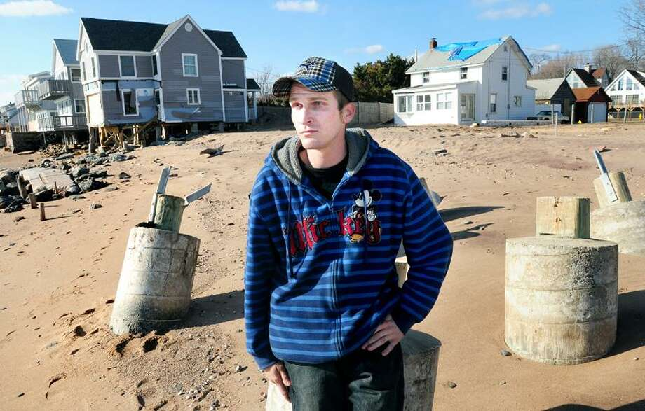 Shawn Hopkinson of East Haven sits on a concrete piling where a house once stood at Cosey Beach in East Haven. Hopkinson set up the relief organization, People Helping People, at Cosey Beach after Hurricane Irene. Arnold Gold/Register