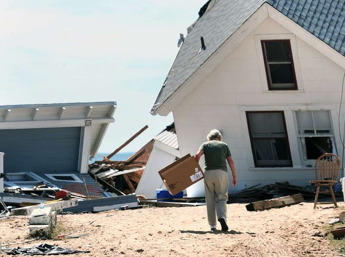 A woman walks toward demolished houses as people began recovering possessions and cleaning up on Cosey Beach Avenue in East Haven. Peter Casolino/New Haven Register