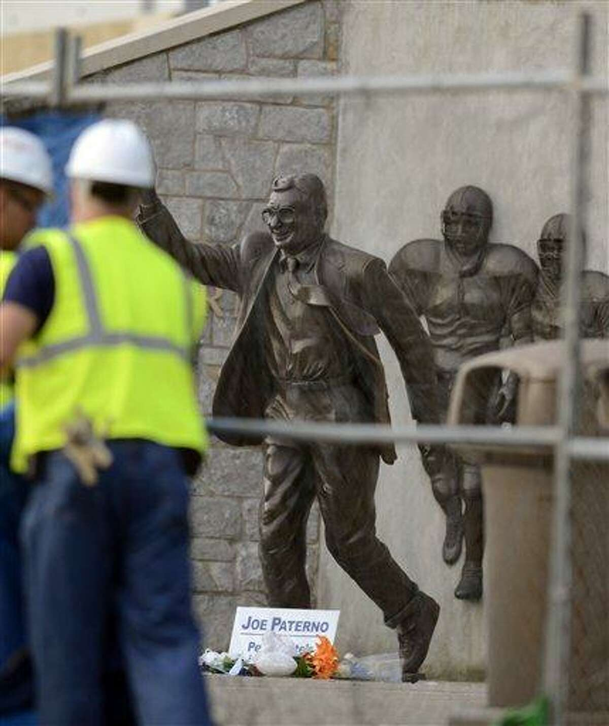 Workers place a tarp on a fence in front of the statue of former Penn State football coach Joe Paterno before removing the statue Sunday in State College, Pa. Associated Press