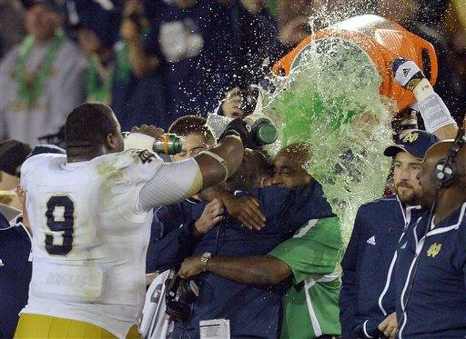 Notre Dame coach Brian Kelly, center left, is doused as he hugs an unidentified team member after Notre Dame defeated Southern California 22-13 in an NCAA college football game, Saturday, Nov. 24, 2012, in Los Angeles. (AP Photo/Mark J. Terrill) Photo: ASSOCIATED PRESS / Mark J. Terrill2012