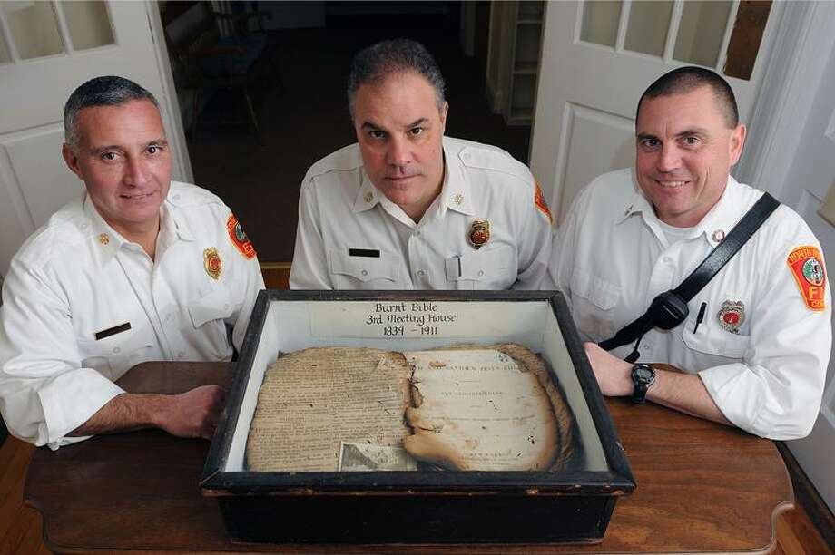 "The North Haven Fire Department was started in 1912 after a fire destroyed the North Haven Congregational Church in 1911. The department celebrates its 100th birthday this year. One of the only things that survived the fire was a partially burnt bible. Shown with the historic relic is Chief Vincent Landisio, center, Deputy Chief David Marcarelli, left, and Lt. Jeff O'Bier, the department's ""historian.""   Peter Casolino/Register"