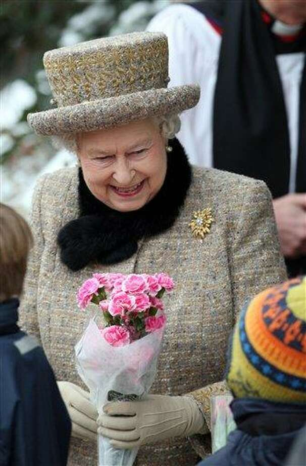 Britain's Queen Elizabeth II accepts a bouquet of flowers from a well wisher at the church of St Peter and St Paul at West Newton, eastern England, Sunday. The queen braved the cold and snow to attend church Sunday on the eve of her Diamond Jubilee anniversary. The 85-year-old monarch marks 60 years on the throne on Monday. The anniversary will be marked by a series of regional, national and international events throughout 2012. Elizabeth ascended the throne when her father, George VI, died on Feb. 6, 1952. She is the longest-serving monarch after Queen Victoria, who reigned for more than 63 years. Associated Press Photo: AP / PA