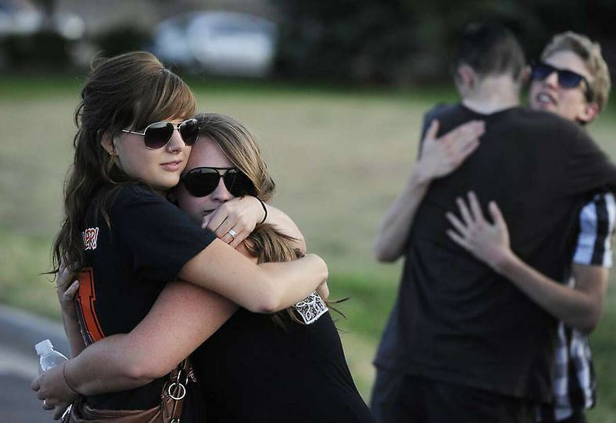 Friends Jessica Bacon, left, and Sarah Hewitt, right, along with good friends hug each other during a vigil across the street from the Century 16 MovieTheaters at the Aurora Town Center Friday, July 20th, 2012, the scene of mass shooting in which 12 people were killed and over 50 were shot and injured. Andy Cross, The Denver Post
