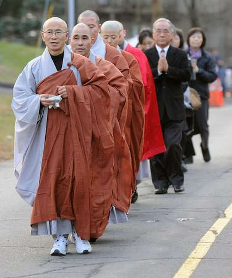 Staff photos by Tom Kelly IV A group of Buddhist monks, from numerous seminaries in Connecticut and New York, pray and walk from downtown Sandy Hook to the memorial at the entrance to Sandy Hook Elementary School. Funerals for two, six year old students from the Sandy Hook Elementary School in Newtown, CT took part Tuesday December 18, 2012. Mourners paid their respects at the Saint Rose of Lima Church. / © 2012 Tom Kelly IV