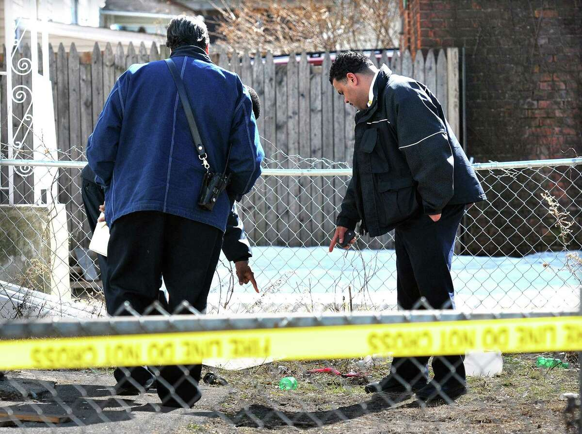 New Haven-- New Haven Fire Department Arson investigators look at what appear to be soda bottles in the rear of 56 Maltby Place. Photo by Peter Casolino/New Haven Register03/04/11 Cas110304