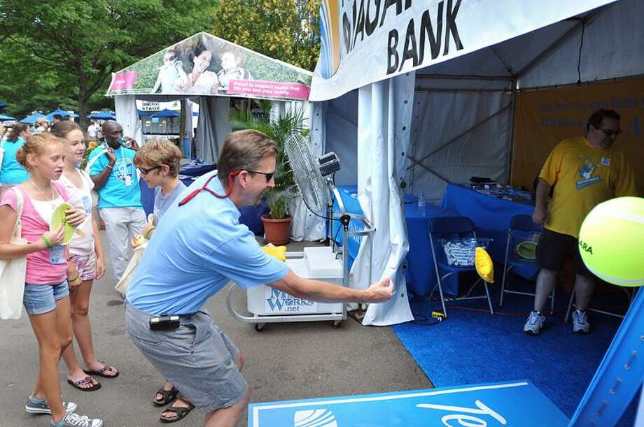 Chuck Imbergamo of Madison plays a bean-bag toss game Monday at the First Niagara Bank sponsor tent at the New Haven Open at Yale. (Peter Casolino/Register)