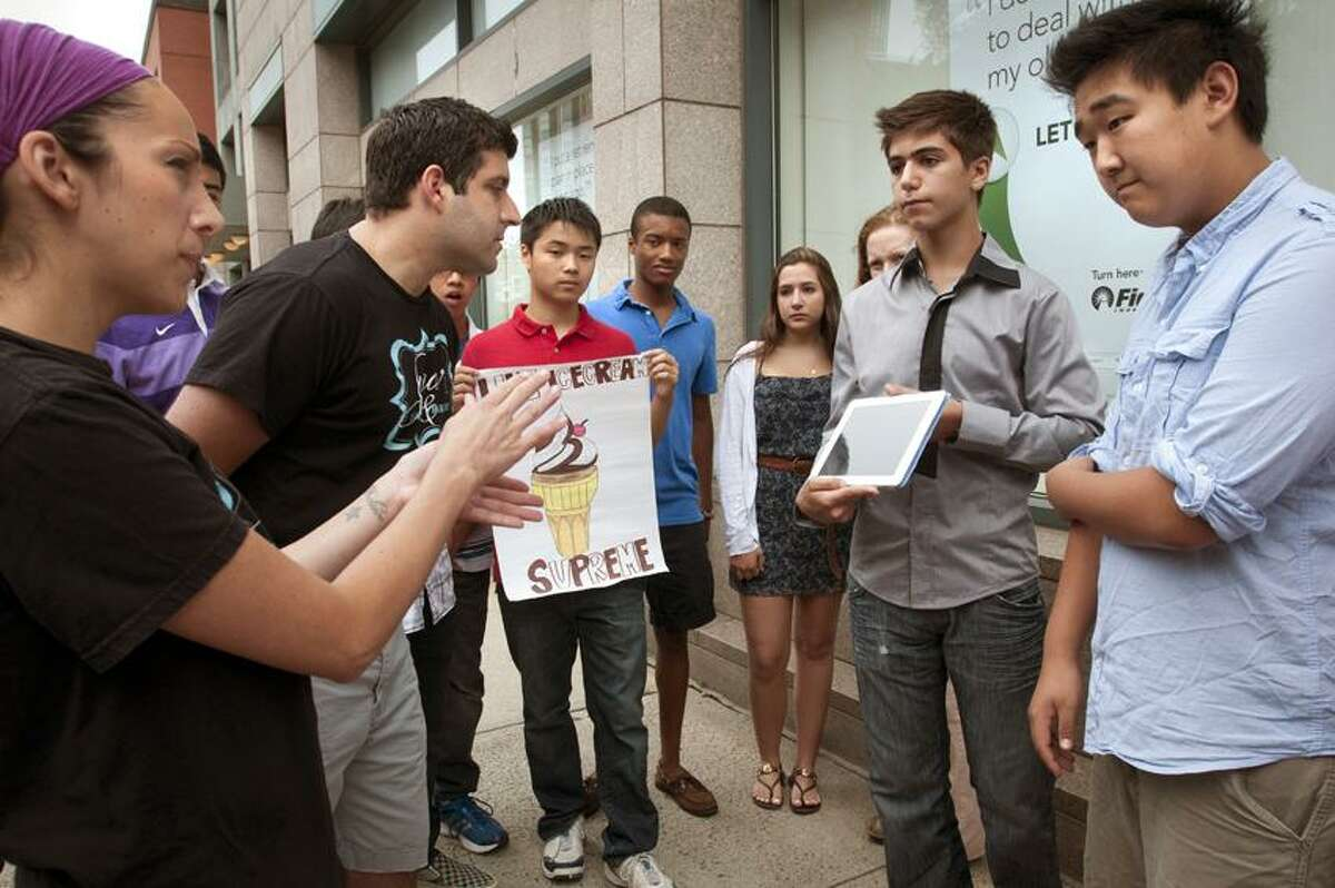Brenda and Michael dePonte Co owners of Sugar Bakery in East Haven (L) look over campaigns from Ad Smart and Momentum; two student groups competing to promote a new cupcake flavor for the bakery. The competition was part of a marketing class taught at the Summer Institute at Yale. The class was taught by Ingrid Ellinger Doviak. Melanie Stengel/Register