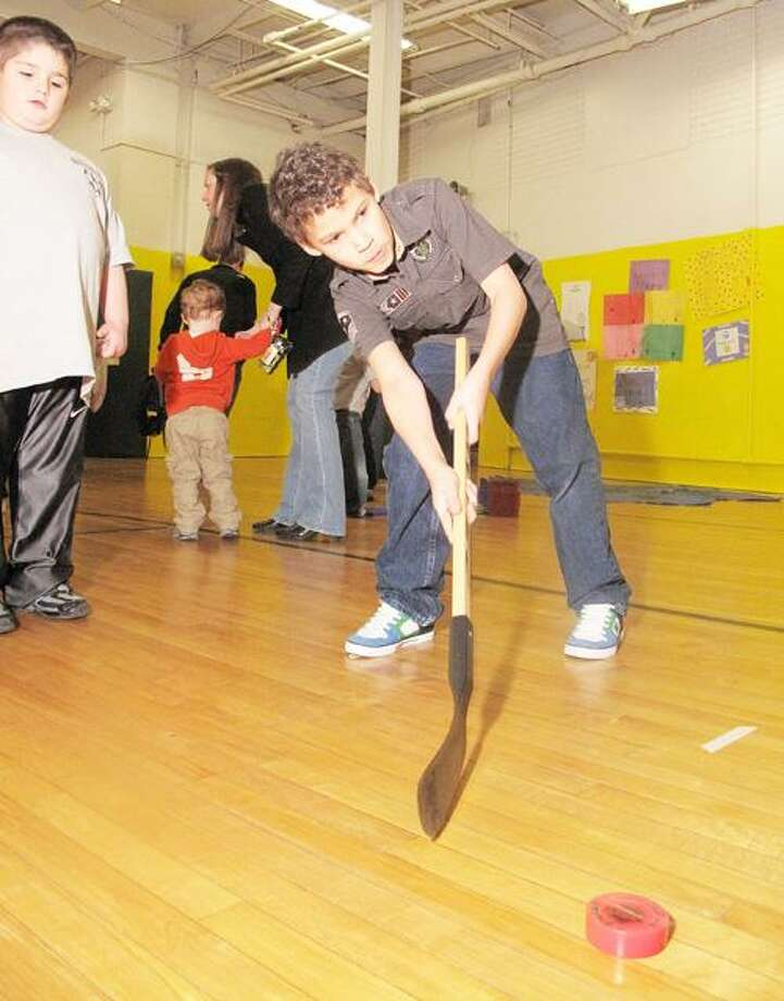 Photo by JOHN HAEGER (Twitter.com/OneidaPhoto) Nate Jennings, 9, of Oneida, tests his stick skills as he tries to hit the puck into the goal during St. Patrick School's Open House and Carnival on Saturday, Feb. 4, 2012, held at the school in Oneida.
