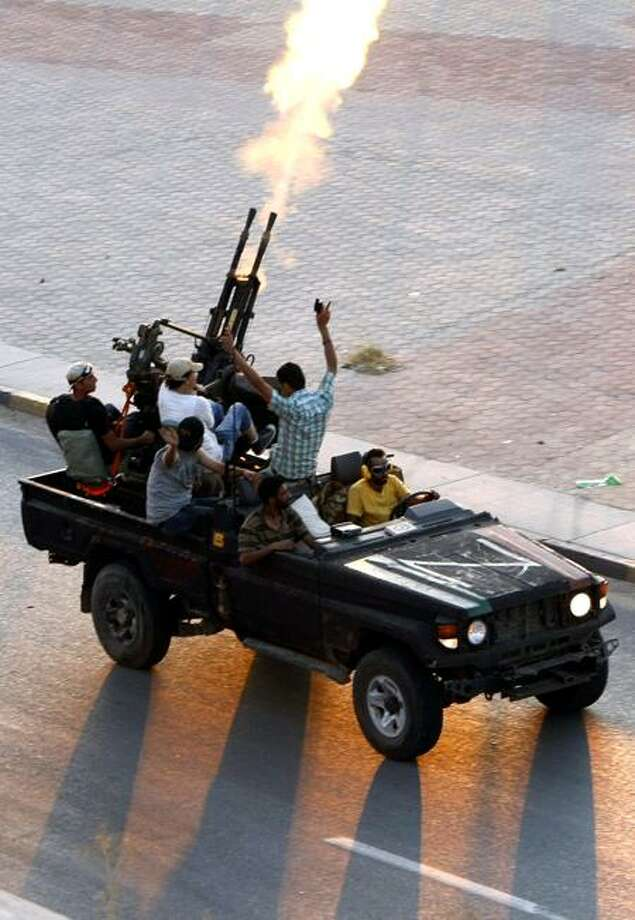 Rebels fire into the air in the Bab El Bahrah district in Tripoli Tuesday.   Associated Press