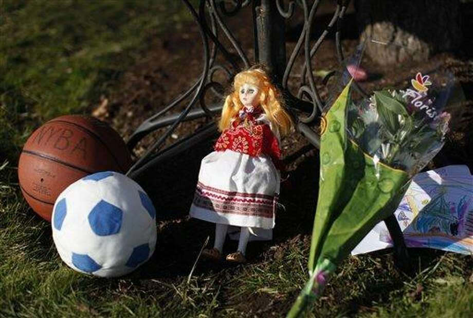 A basketball, soccer ball, doll, flowers and a child's drawing sit at a memorial for shooting victims outside Saint Rose of Lima Roman Catholic Church Saturday in Newtown. (AP Photo/Jason DeCrow) Photo: AP / 2012 AP