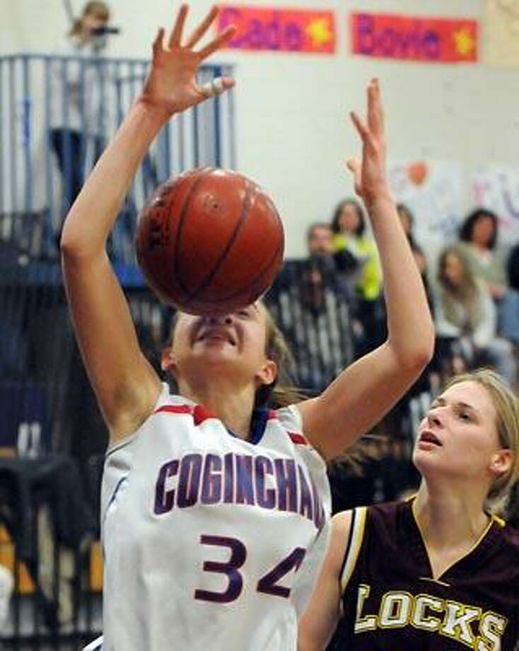 Class S girls basketball tournament, Windsor Locks at Coginchaug (Durham), second quarter. Coginchaug's Jessica Solomon appears to go nose-to-nose with a loose ball.  Windsor Locks' Jenna Wojtas at right. Photo by Mara Lavitt/New Haven Register3/3/11