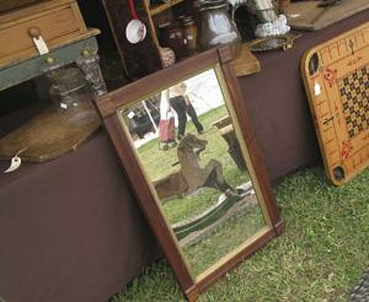 Dispatch Staff Photo by JOHN HAEGER A shopper pulling a cart is reflected in a mirror as she walks by on the main field of the Madison Bouckville Antiques Show on Saturday, August 21, 2010.