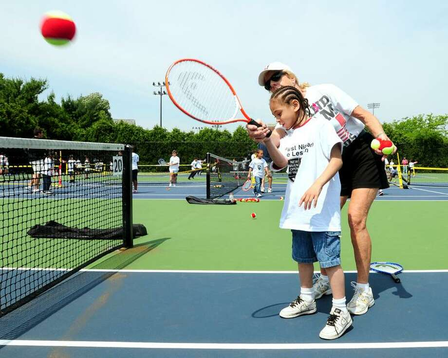 Barnard Environmental Studies School first grader Edgardo Cardona, 6, is taught a forehand by Coach Bunny Logan of Valley Regional High School during a free tennis clinic for New Haven school children at the Connecticut Tennis Center in New Haven. The event was sponsored by First Niagara, one of several sponsors taking an active role in the New Haven Open at Yale. (Photo by Arnold Gold/New Haven Register)