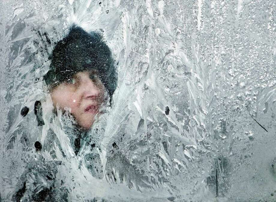 A woman looks out of a window covered in frost on a bus in Bucharest, Romania, Thursday. At least 11,000 villagers have been trapped by heavy snow and blizzards in Serbia's mountains, authorities said Thursday, as the death toll from Eastern Europe's weeklong deep freeze rose to 122, many of them homeless people. (AP Photo/Vadim Ghirda) Photo: ASSOCIATED PRESS / AP2012