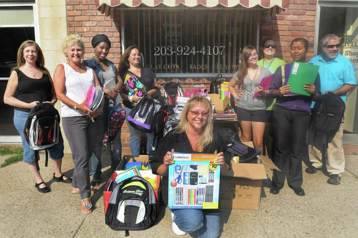 Jennifer Shneider (front center) of J Cuts salon in Shelton, distributed donated school supplies to representatives of Valley nonprofit agencies this week. Her business was a collection site at which area residents dropped off donated back-to-school supplies for children in need. (Photo by Melanie Stengel/Register)