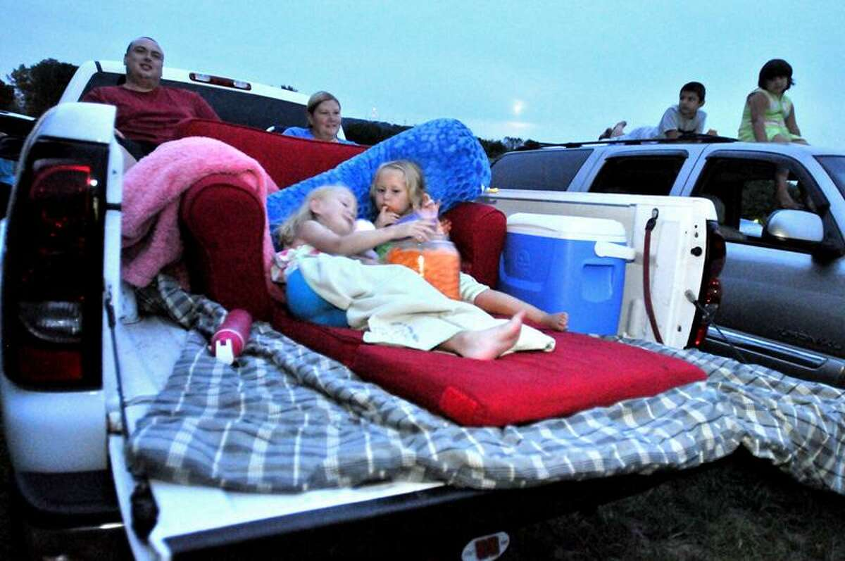 The DeLeo family of Prospect prepares for a Saturday night feature in the back of the family pick-up truck. Back row: Rob DeLeo, Sarah DeLeo, Front Row: Sophia DeLeo, 6 and Olive DeLeo, 3. Photo by Brad Horrigan/Register