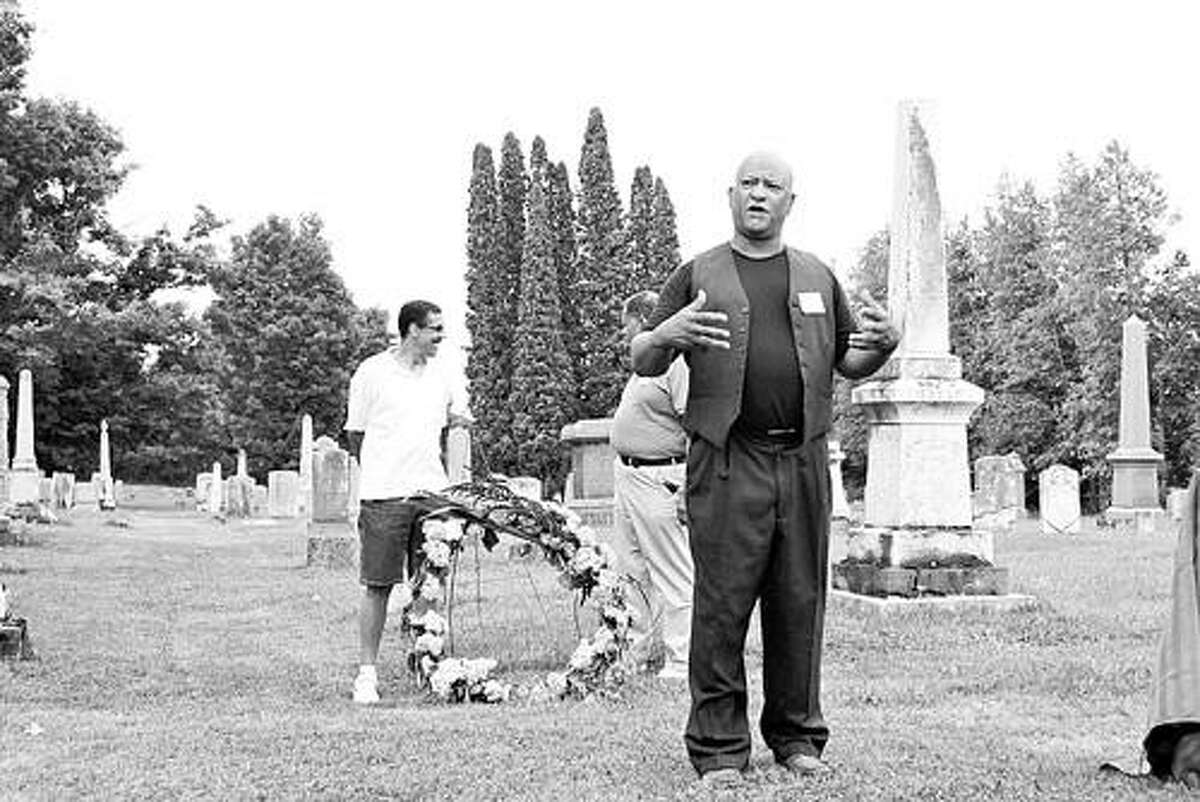 """Submitted Photo In this monochrome photo, Jim Corpin readies the wreath for William """"Billy"""" Smith's gravestone and Max Smith gives a brief history of Smith, who was born a slave and died a free man. Corpin and Smith are co-chairs of the second annual Peterboro Emancipation Day held Aug. 6."""
