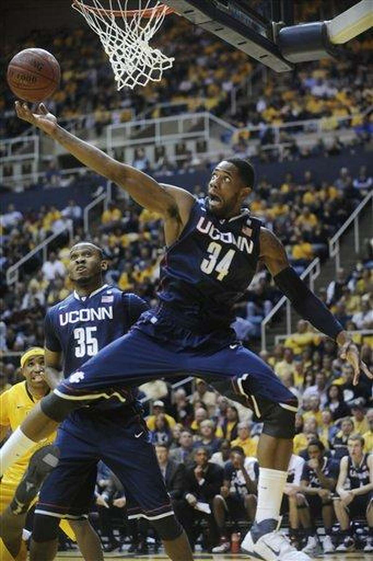 Connecticut's Alex Oriakhi (34) pulls down a rebound against West Virginia, Wednesday, March 2, 2011, during the first half of an NCAA college basketball game in Morgantown, W.Va. (AP Photo/Jeff Gentner)