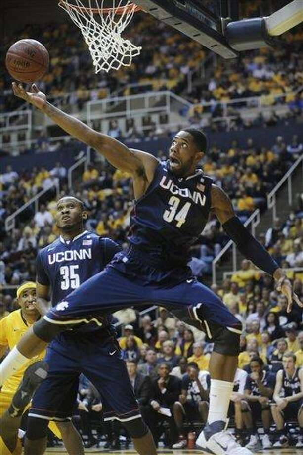 "Connecticut's Alex Oriakhi (34) pulls down a rebound against West Virginia, Wednesday, March 2, 2011, during the first half of an NCAA college basketball game in Morgantown, <a href=""http://W.Va"">W.Va</a>. (AP Photo/Jeff Gentner) Photo: AP / FR123894 AP"