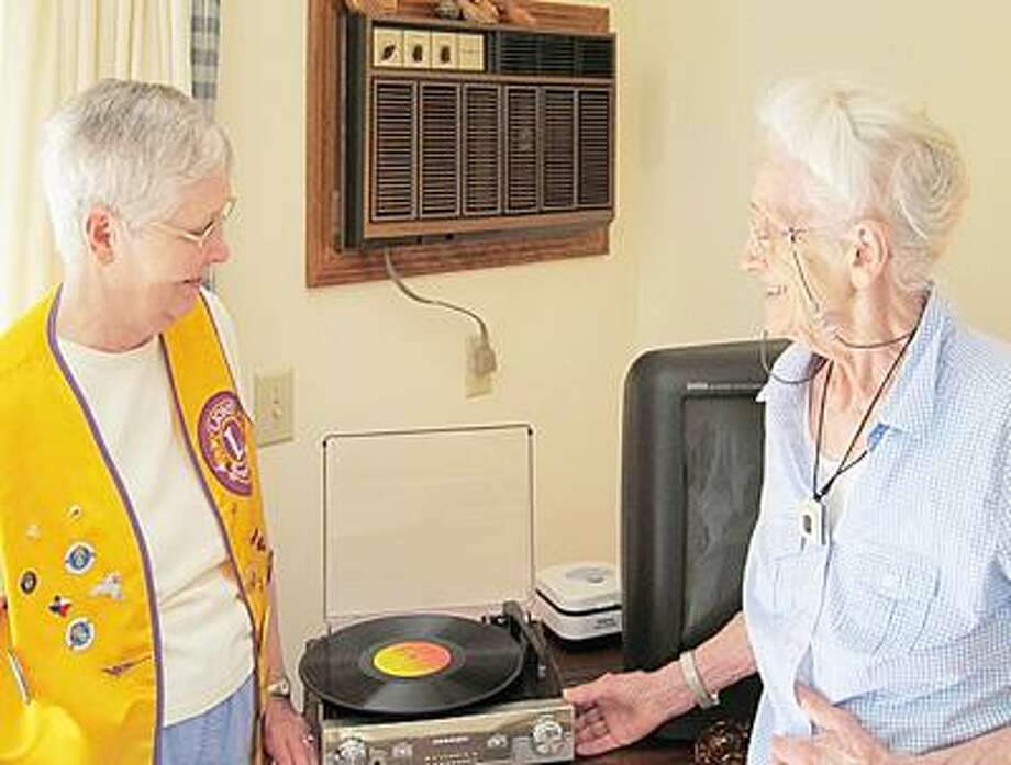 SUBMITTED PHOTO Chittenango Lion Joan Grover presents a new phonograph to Betty Yates.