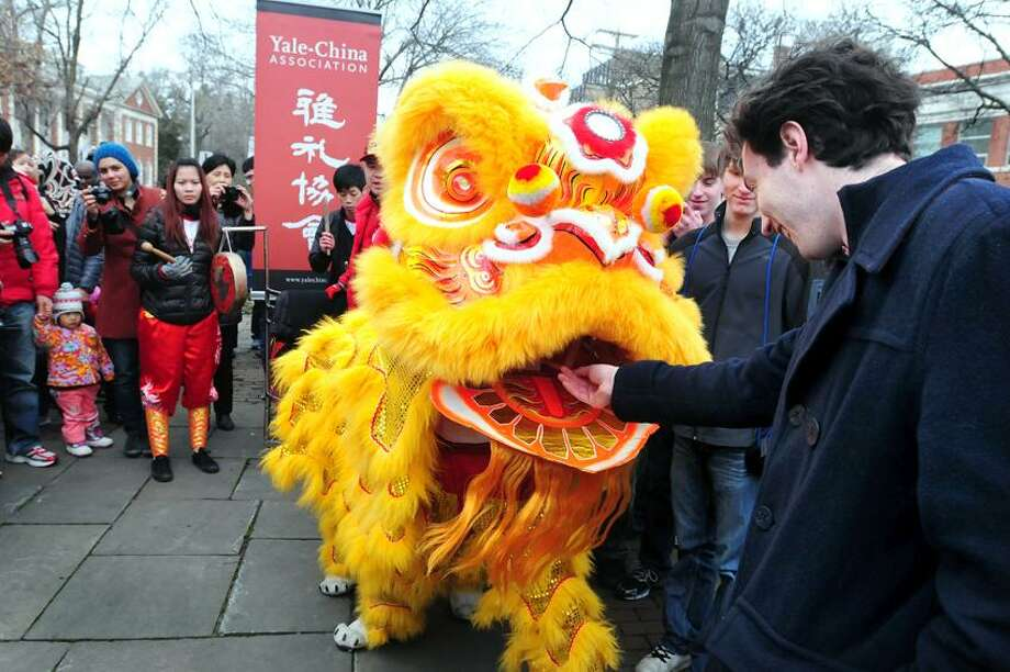 Paul Kruse (right) of Hamden puts an envelope with money into the mouth of a dancing lion at Phelps Triangle Park in New Haven during a Lion Dance Parade organized by the Yale-China Association for the Chinese New Year on 2/2/2012.  The Wan Chi Ming Hung Gar Institute Dragon and Lion Dance Team from New York City performed for the parade.Photo by Arnold Gold/New Haven Register   AG0437E