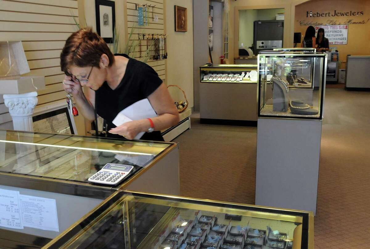 Patricia Antonini of Milford looks over the items for sale at Hebert Jewelers, which is liquidating merchandise as it prepares to close. (Photo by Mara Lavitt/New Haven Register)