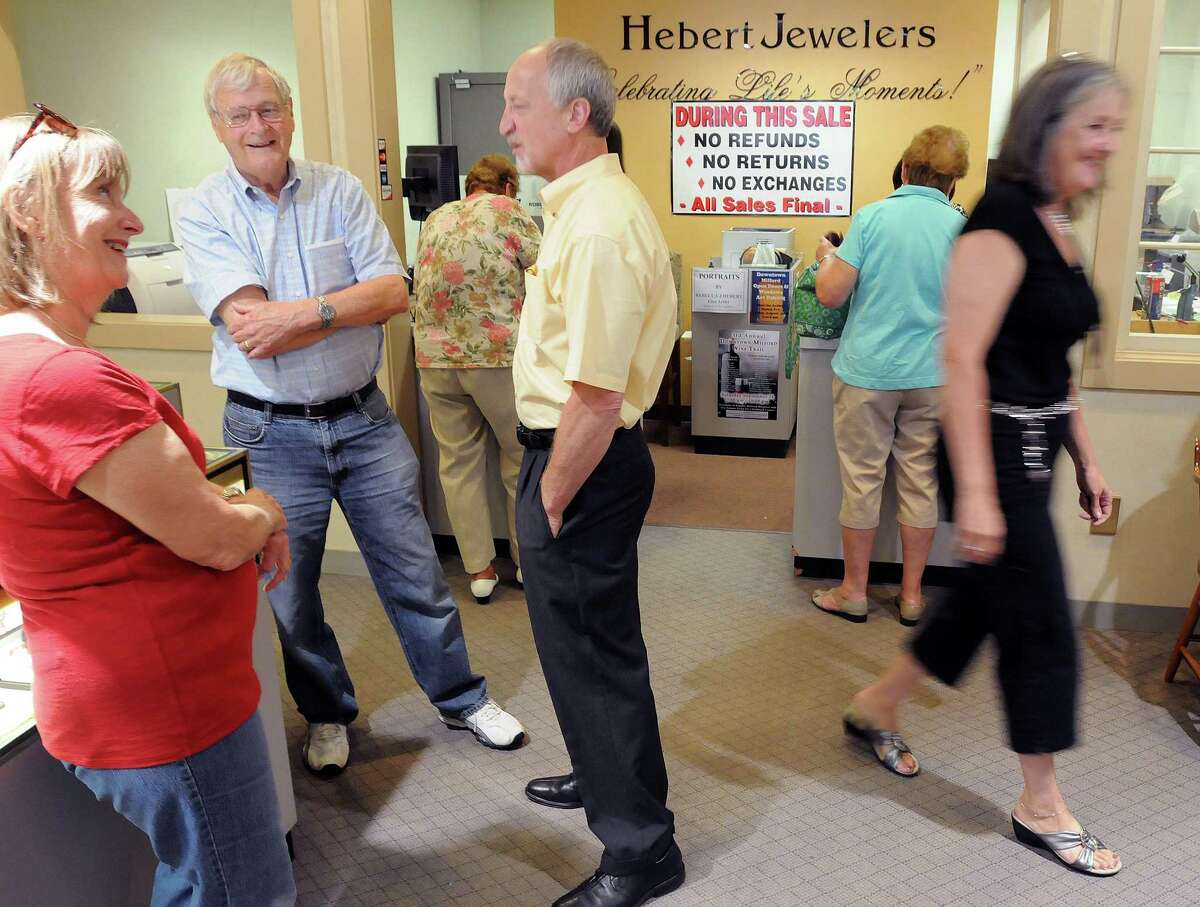 Barbara and Chuck Sommers of Milford, left, chat with Joseph Hebert, center, while his wife Louise Hebert goes to help another customer. Hebert Jewelers is closing after 58 years in business. (Photo by Mara Lavitt/New Haven Register)