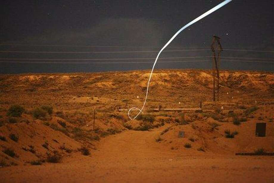 In this undated photo provided by Sandia National Laboratories, a time exposure, a light-emitting diode, or LED, attached to a self-guided bullet at Sandia National Laboratories shows a bright path during a nighttime field test. Associated Press Photo: ASSOCIATED PRESS / AP2012
