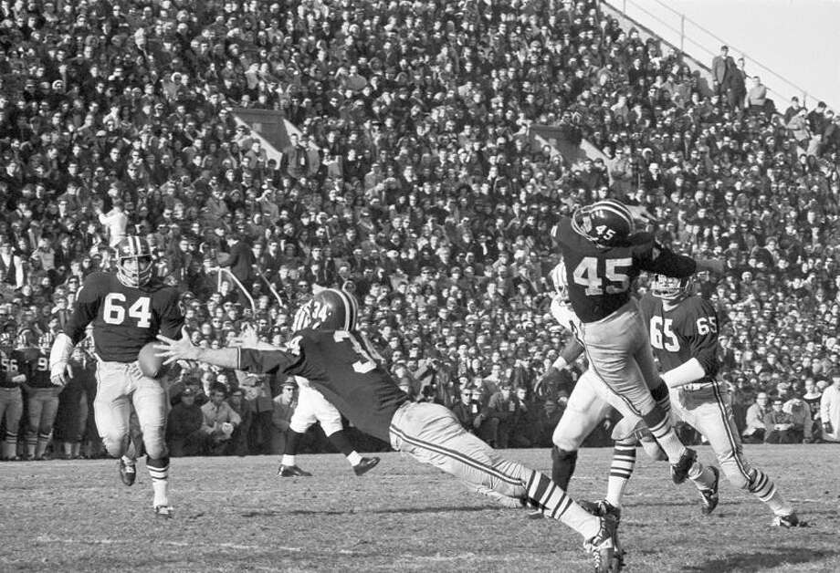 Harvard's Pat Conway dives to try to intercept a Brian Dowling pass intended for Yale's Calvin Hill, both not shown, after the ball gets past Tom Wynne (45) during the second quarter of The Game at Harvard Stadium on Nov. 23, 1968. Harvard's Gary Farneti (64) is at left. Both teams finished the season unbeaten when the game ended in a 29-29 tie. (Associated Press file photo) Photo: ASSOCIATED PRESS / AP1968