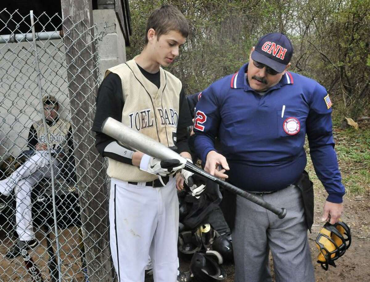 Kieran Geyer (L), of Barlow, checks his bat with umpire Fred Norman before the start of the game against Platt. Melanie Stengel/Register