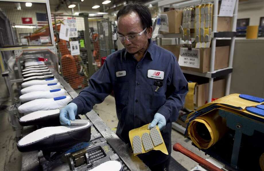 In this Tuesday, May 1, 2012, file photo, worker Khan Simom, of Boston, glues cushions to unfinished shoes during the assembly process at the New Balance Athletic Shoe, Inc. factory in Boston. .S. companies added to their stockpiles in May, but their sales fell for a second straight month. Business stockpiles grew 0.3 percent in May from April, matching April's increase, the Commerce Department reported Monday, July 16, 2012. Total business sales fell 0.1 percent in May, matching the April decline. Associated Press Photo: AP / 2012 AP